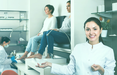 happy woman nail technician welcoming visitors to modern beauty salon
