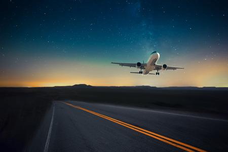 Airplane flying high in dark night sky against desert-like landscape Stock Photo