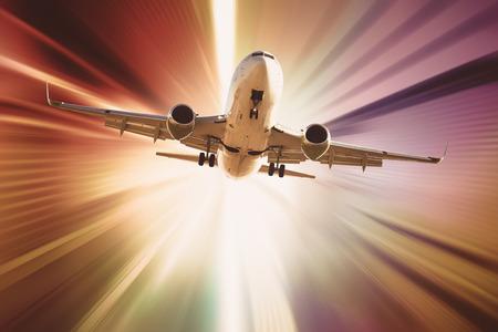 Passenger aircraft flying in sky in divergent glar sunlight Stock Photo