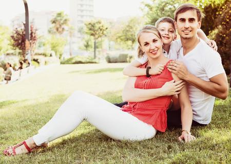 Jeune parent heureux avec garçon de l'âge de l'adolescence assis sur l'herbe verte dans le parc Banque d'images - 80304067
