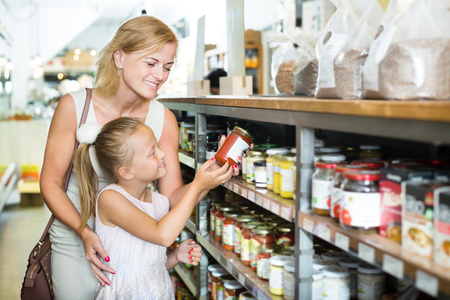 Glad young mother with daughter shopping conserve crushed tomatoes in a groceries. Focus on child