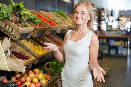 Portrait of  beautiful charming woman buying fresh greens and fruits in grocery shop Stock Photo