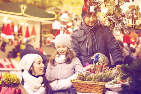 festal: Positive family of four choosing floral decorations at market. Focus on brunette girl Stock Photo