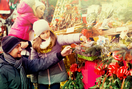Happy family of four choosing floral christmas decorations at market together. Focus on man and girl Stock Photo