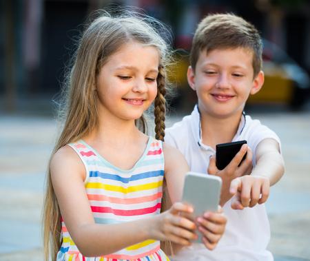 Retrato de dos niños sonrientes alegres jugando con teléfonos móviles juntos al aire libre. Centrarse en chica Foto de archivo - 80192580