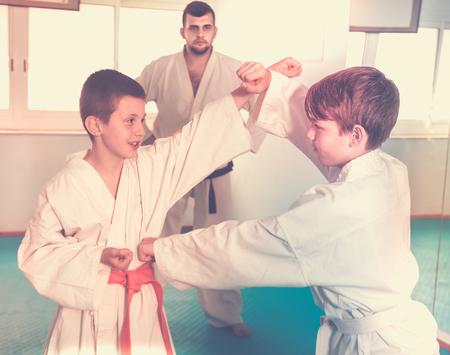 techniek: Jonge jongens trainen in paar om karate techniek te gebruiken tijdens de les