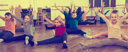 Boys and girls with trainer stretching in dance hall