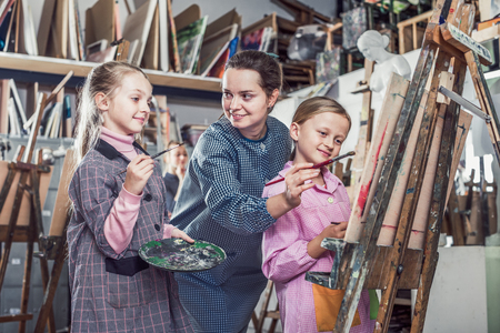 neatness: Young female teacher giving master class during painting class at art studio