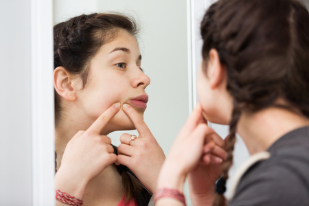 Young girl cleaning pores in front of mirror at home