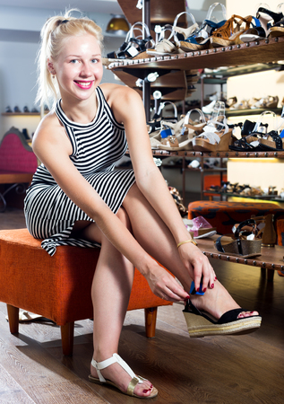 Portrait of young cheerful woman fitting picked footwear in fashion boutique