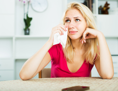 Portrait of young crying blonde waiting for call sitting indoors Stock Photo