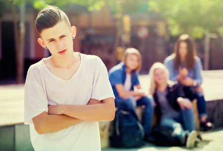 mobbing: Lonely teenager standing away from friends feeling depressed Stock Photo