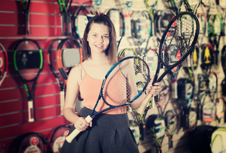 keep in touch: Smiling young woman holding in hand racket for badminton in sport shop Stock Photo