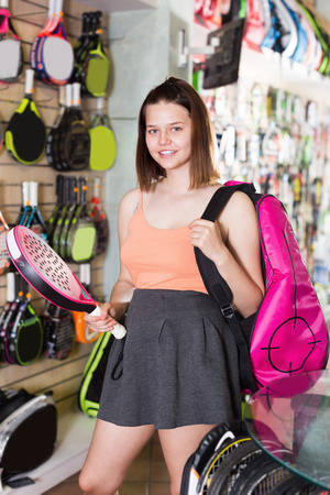 happines: Cheerful teen girl holding in hand racket for squash in sport store