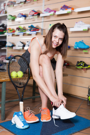 happines: Positive teen girl trying professional sneakers in sport store Stock Photo