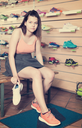 happines: Cheerful young sportswoman trying professional shoes in sport shop