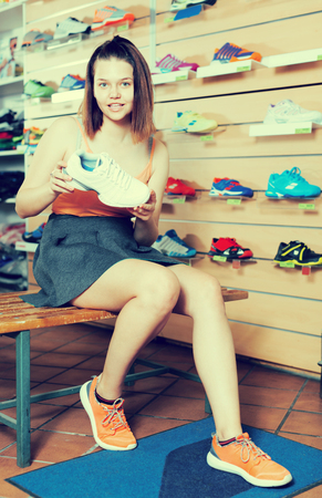 keep in touch: Smiling young sportswoman trying professional shoes in sport shop