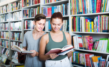 Two positive teenagers reading book together while choosing new literature in shop Stock Photo