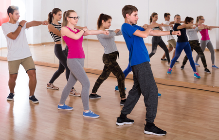 Group of positive smiling american teenagers dancing   in classroom Stock Photo