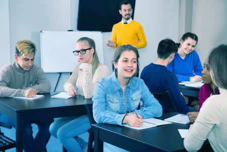 Diligent  smiling fellow students having group work tasks during school day Stock Photo