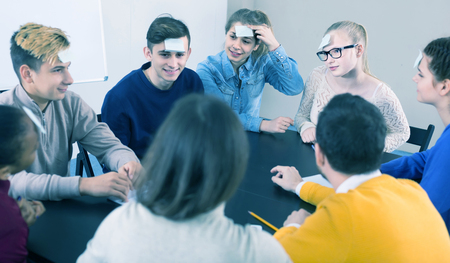 animated boy: positive spanish  classmates having round of guess-who game during class
