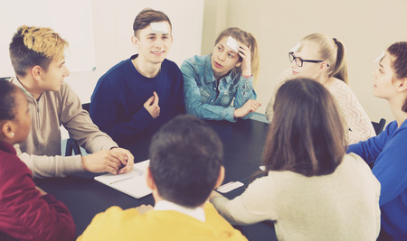 animate: Happy male and female students playing guess-who game in school Stock Photo
