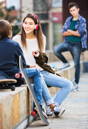 16s: Upset male teen standing aside of girlfriend talking with boy outdoors Stock Photo