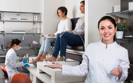 cheerful woman nail technician welcoming visitors to modern beauty salon