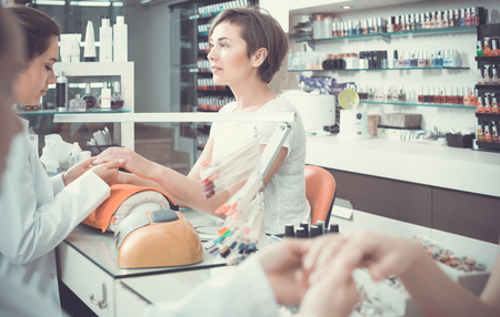 attentive female manicurist filing and shaping nails during procedure of manicure in beauty salon
