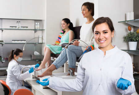 Portrait of happy european professional nail master at working place inviting to salon Stock Photo