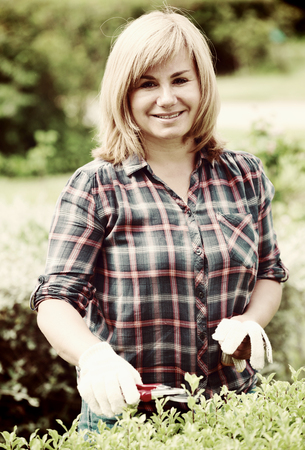 smiling blond mature woman  holding horticultural tools in garden on sunny day Stock Photo
