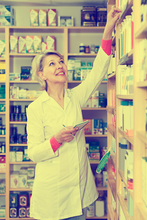 specialized job: Adult woman seller writing down assortment of care products in shop Stock Photo
