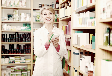 adult  body writing: Nice woman seller writing down assortment of care products in shop