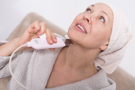 habitual: Elderly woman performing ultrasonic face cleaning with device at home
