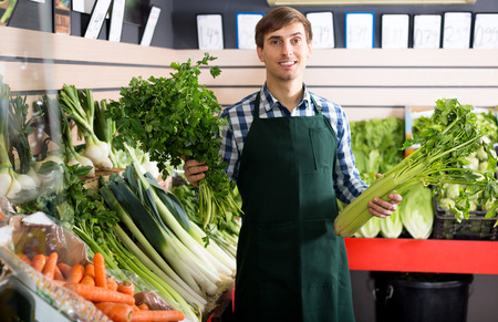 Happy male seller posing with celery, parsley and leek in store