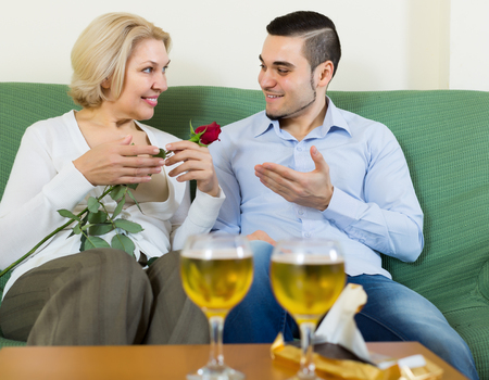 Happy guy and elderly woman drinking wine and smiling