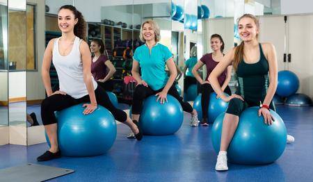 Lächelnde Frauen, die aerobe Übungen mit Schweizer Ball im Fitness-Club haben. Selektiver Fokus Standard-Bild - 80355225