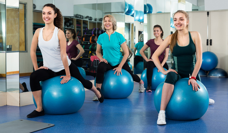 Smiling females having aerobic exercises with Swiss ball in fitness club . Selective focus Stock Photo - 80355225