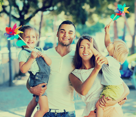 freetime: Positive young parents holding kids with toy windmills at summer day