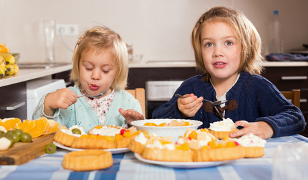 Two happy little girls enjoying pastry with cream in kitchen at home
