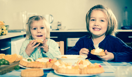5s: Two happy smiling little sisters enjoying pastry with cream in kitchen at home