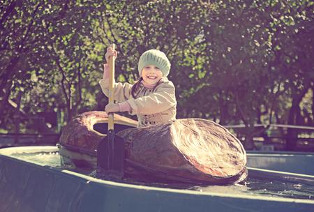 Happy little girl swims by boat in amusement park