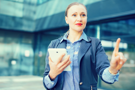 Adult professional woman in jacket with tablet pointing finger on air