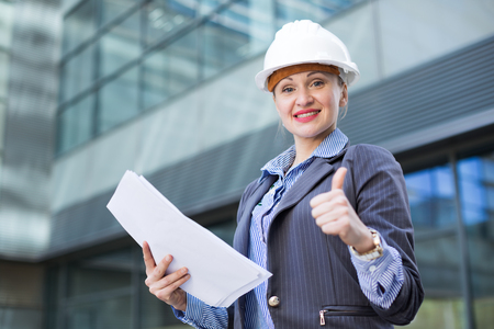 Employee woman in suit standing in helmet with paper documents
