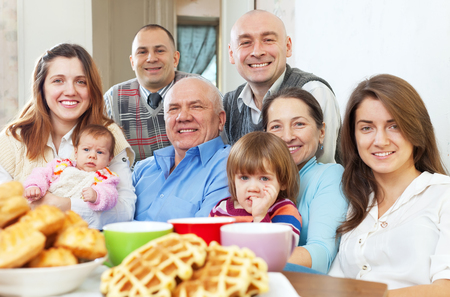 Portrait of  large three generations family drinks tea with baked at home Stock Photo