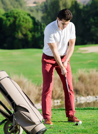 readiness: smiling spanish man playing golf is going to hit ball at golf course Stock Photo