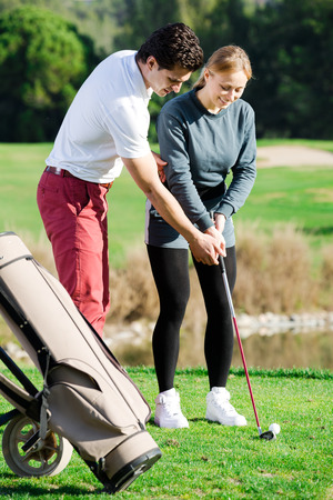 Handsome male golf trainer showing female player how to hit ball rightly
