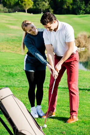 brassy: Beautiful woman golfer training man to play golf and hit ball correctly