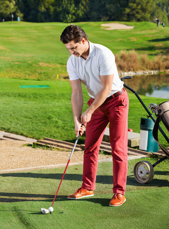 brassy: Young glad  positive  man preparing to hit ball at golf course