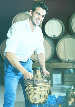 wicker work: Glad man holding big wicker bottle with wine in store with woods